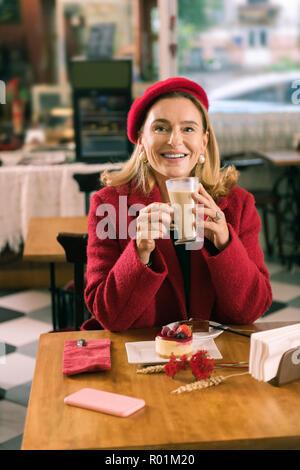 Strahlende blonde Frau mit roten Mantel und Baskenmütze Kaffee trinken - Stockfoto