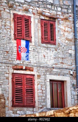 Kroatische Flagge unter roten Fensterläden Fenster in Sibenik Kroatien. - Stockfoto