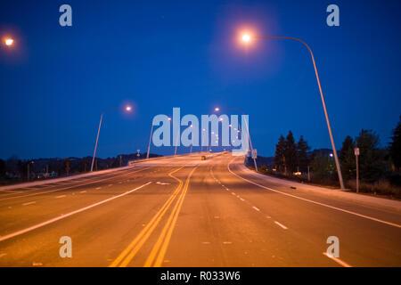 Autobahn durch die Straßenlaternen nachts beleuchtet aufgegeben. - Stockfoto