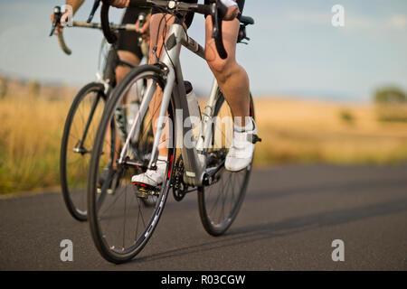 Reifes Paar Radfahren entlang einer Landstraße. Stockfoto