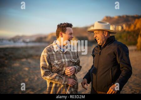 Teenager Sohn und seine im mittleren Alter Vater Lachen, während sie ein Witz miteinander teilen, wie Sie am Strand bei Sonnenuntergang spazieren. - Stockfoto