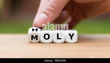 """Hand dreht einen Würfel und Änderungen das Wort """"heilig"""" zu Oly 'm' - Stockfoto"""
