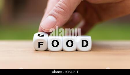 Hand dreht einen Würfel und Änderungen das Wort 'gut' zu 'Nahrung' - Stockfoto