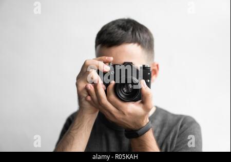 Hübscher junger bärtiger Mann in einem schwarzen T-Shirt, Vintage altmodischen Film Kamera auf einem weißen Hintergrund und Suchen in den Suchermodus der Kamera. - Stockfoto