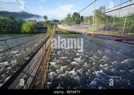 Gemeinsame Brücke Gehweg Fluss in Borneo Innenraum zu überqueren. - Stockfoto