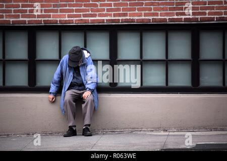 Obdachlosen, das an der Wand saß - Stockfoto