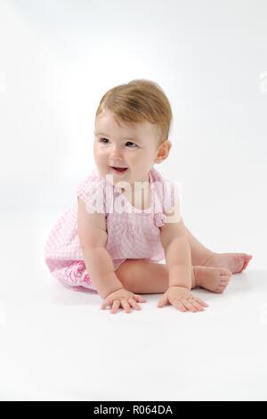 Eine junge und weiblich Kaukasier Kind an jemand aus Kamera lächelnd. Eine vertikale Portrait Farbe Bild fotografiert in einem Studio. - Stockfoto