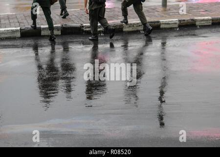 Reflexion von Menschen zu Fuß auf nasser Straße im regnerischen Tag - Stockfoto