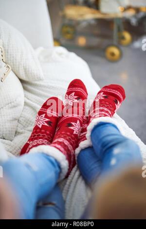 Ein paar Verlegung auf dem Sofa und das Tragen der roten Weihnachten themed Socken. - Stockfoto
