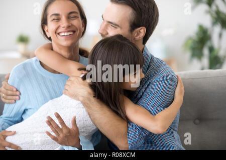 Entzückende Tochter im Vorschulalter umarmt Glücklich lächelnde Eltern - Stockfoto