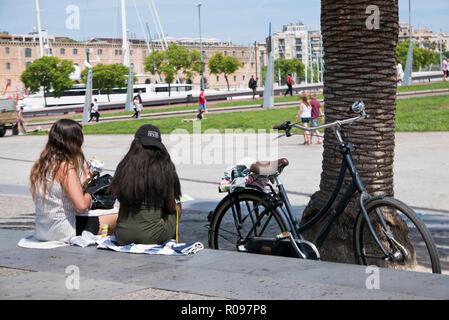Zwei junge Frauen sitzen auf dem Bürgersteig und ein Mittagessen mit einem Fahrrad durch ihre Seiten, Barcelona, Spanien - Stockfoto