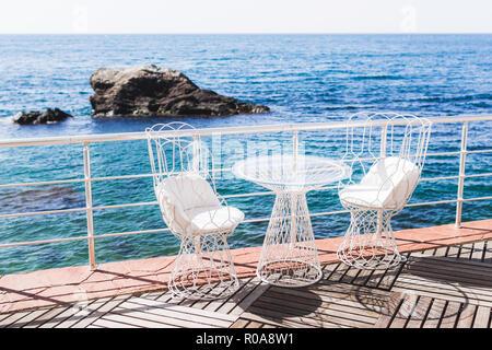 Сafe mit weißen Tischen vor dem Meer - Stockfoto