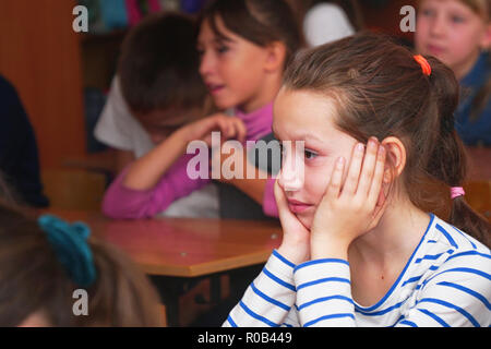 Schülerin in der Klasse, dem Lehrer zuhören