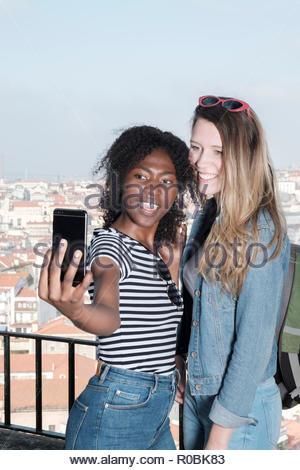 Zwei Freunde, einer afrikanischen, europäischen unter selfies zusammen in Lissabon, Westeuropa - Stockfoto