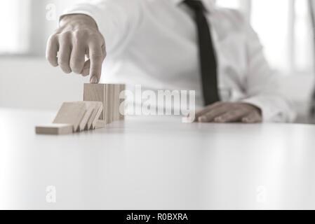 Nahaufnahme an Hand des Geschäfts Mann stoppen fallende Blöcke auf Office Tabelle für Konzept zum Management. - Stockfoto