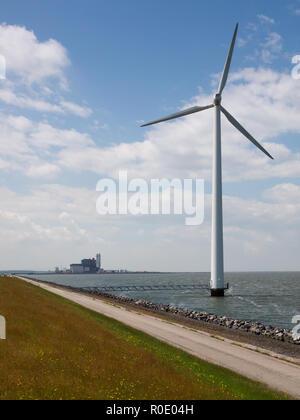 Eine Windenergieanlage mit einem fossilen Kraftwerk im Hintergrund getankt - Stockfoto