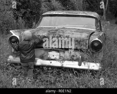 Ein kleiner Junge ist ein altes Auto berühren. - Stockfoto