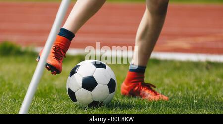 In der Nähe der jugendlichen Fußballspieler Kicking Kugel auf dem Fußballfeld. Fußball Eckball auf dem Spielfeld. Fußballer der Roten Stollen auf dem grünen Rasen der Sta - Stockfoto