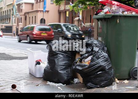 Plastiktüten und einem überquellenden Mülleimer voll Abfall in Macquarie Street im Herzen von Sydney, Australien - Stockfoto