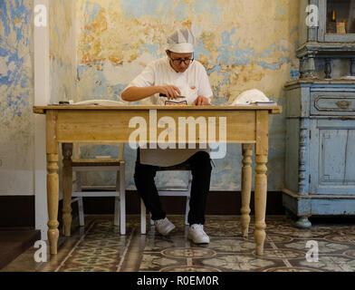 Gallipoli, Italien. Frau sitzt an einem Tisch und macht Pasta Orecchiette, Ohr geformt, die traditionell für die Region Apulien in Italien. - Stockfoto