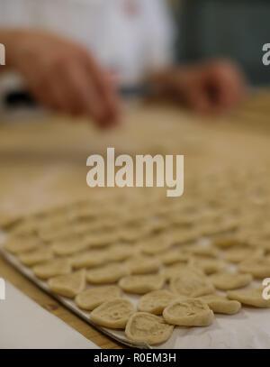 Nahaufnahme von Pasta. Frau macht Pasta Orecchiette, Ohr geformt, traditionell bis Apulien, Italien. Hände sind schnell und sind ein Unschärfe - Stockfoto