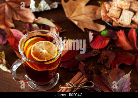 Eine Tasse Kaffee steht auf einem Tisch mit Herbstblättern übersäten - Stockfoto