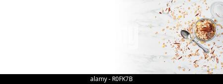Draufsicht auf das gesunde Frühstück. Jar Gesunder Joghurt mit Erdbeersauce, Hafer und Schokolade auf weißem Marmortisch. Banner mit kopieren. - Stockfoto