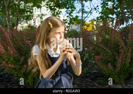Schülerin 8 Jahre alte Eis essen. Blonde Mädchen in Schuluniform, Hintergrund, grüne Bäume, Hof. - Stockfoto