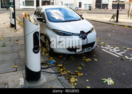 Weiß Renault Zoe Dynamique NAV Elektroauto aufladen an curbside Ladestationen. - Stockfoto