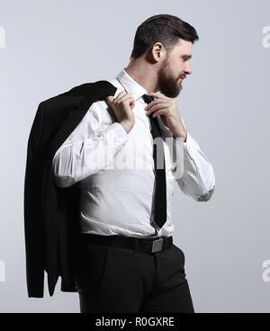 Geschäftsmann, der seine Jacke über die Schulter und richtet seine Krawatte - Stockfoto