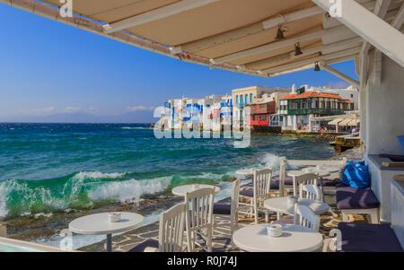 Blick auf die berühmte malerische kleine Venedig auf der Insel Mykonos. Plätschernden Wellen über Bars und Restaurants der Altstadt, Kykladen, Griechenland. Stühle mit Ta - Stockfoto