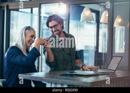 Junge Unternehmer und leitende Geschäftsfrau Bilden einer Faust bump im Büro. Kollegen suchen glücklich und aufgeregt nach Beendigung des Projekts. - Stockfoto