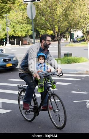 Vater und Kind auf einem Fahrrad in der Nähe von Prospect Park in Brooklyn, New York. - Stockfoto