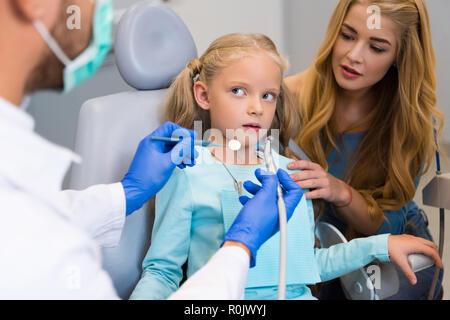 7/8 Schuß von Zahnarzt arbeiten mit verängstigten Kind während Mutter in der Nähe ihrer Sitzung für die Unterstützung - Stockfoto