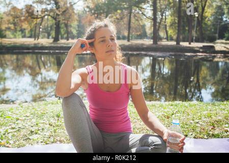 Frau entspannen Sie nach Yoga Übung im Park, Sitzen auf Fitness Matte und die Flasche Wasser. - Stockfoto