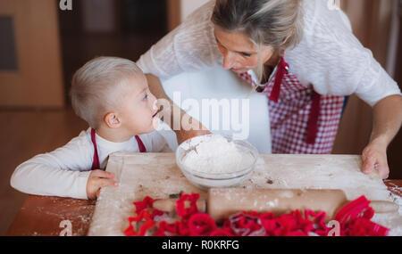 Ein behinderter Down-syndrom Kind mit seiner Mutter zuhause Backen. - Stockfoto