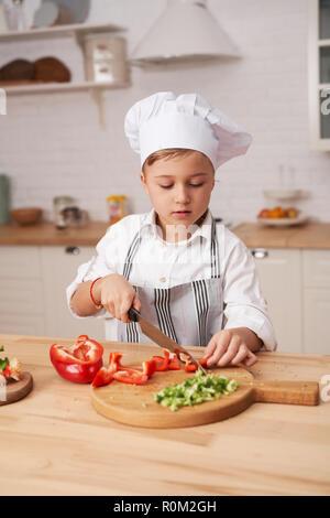 Cute little boy Kochen in der modernen Küche zu Hause. Junge Koch schneidet Gemüse. - Stockfoto