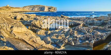Panorama der unnahbar Küstenlinie von Dwejra mit scharfen Kalkstein Felsen, kleine natürliche Pools und mittelalterlichen Wachturm auf dem Hintergrund, San Lawre - Stockfoto
