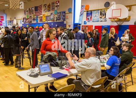 Arlington, Virginia, USA. 6. November 2018. Wahlhelfer prüfen Wähler Identifizierung bei den midterm Abstimmung, an der Schule. Rob Crandall/Alamy leben Nachrichten - Stockfoto