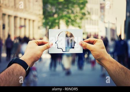 Man Hände halten ein weißes Blatt Papier mit zwei konfrontiert Kopf über einen belebten Straße Hintergrund. Gespaltene Persönlichkeit, bipolare Störung der seelischen Gesundheit Konzept. - Stockfoto