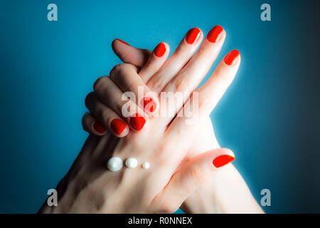 Hände von einem jungen Mädchen mit roten Nägeln und Tropfen Creme close-up auf einem blauen Hintergrund - Stockfoto