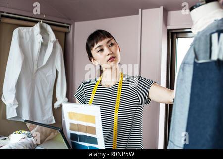 Japanische Frauen Mode Designer arbeiten in ihrem Atelier, am Kleidungsstück auf der Schneiderin Modell suchen. - Stockfoto