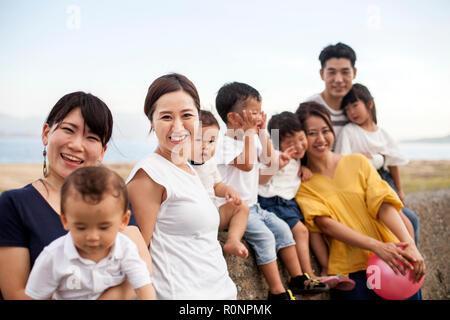 Group Portrait von japanischen Familien mit kleinen Kindern an der Promenade von Ocean, in die Kamera lächeln. - Stockfoto