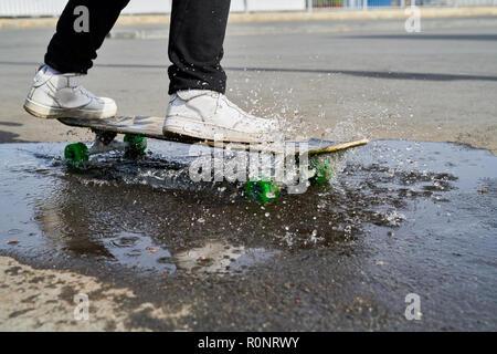 Skater fahren auf Pfütze - Stockfoto