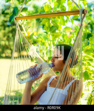 Junge Frau trinkt Mineralwasser aus Plastikflaschen, tropischen Garten, Guadeloupe, Französisch Westindien, - Stockfoto