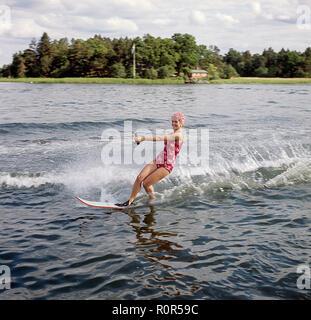 Wasserski in den 1960er Jahren. Eine junge Frau in einem gemusterten Badeanzug übergibt die Fotografen auf ihre Wasserski. Sie hat eine typische Badekappe auf. Schweden 1946 Foto Kristoffersson ref CV 12-7
