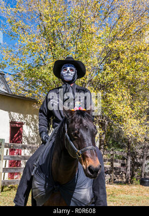 Tag der Toten, Dia de los Muertos, Ghost Rider, Mann, der eine Maske und einen Cowboyhut Reiten eine dunkle Pferd, Lincoln New Mexico, USA. - Stockfoto
