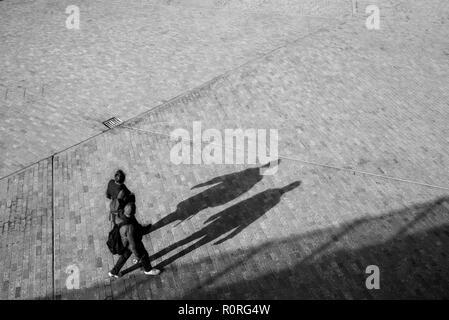 Verschwommen unkenntlich Paar von oben zu Fuß auf einem offenen Raum Platz mit Schatten projizieren auf dem Boden - Stockfoto