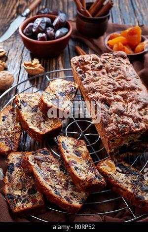 Getrocknete Früchte reich Kuchen auf einem Draht Kuchen stand mit braunem Stoff, Zimtstangen, getrocknete Aprikosen und Datum Früchte auf einem rustikalen Holztisch, vertikale Ansicht - Stockfoto