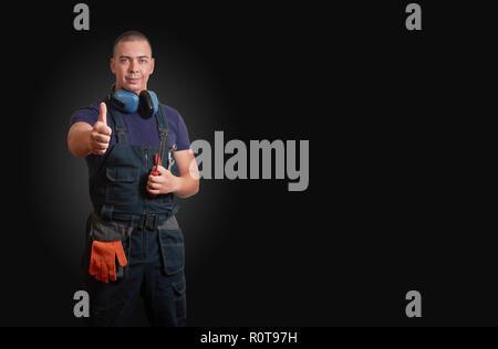 Starke und selbstbewusste männliche Mechaniker in Blau overal stehend mit orange Handschuhe, weißen Helm, Gehörschutz und Tools auf schwarzem Hintergrund - Stockfoto